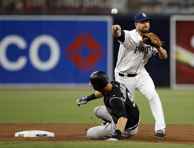 San Diego Padres third baseman Chase Headley, right, makes the force out at second, then throws over Colorado Rockies' DJ LeMahieu, but not in time to get Carlos Gonzalez at first during the first inning of a baseball game in San Diego, Monday, April 2, 2018.