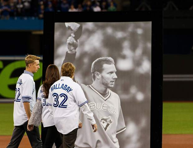 Brandy Halladay, center, and her two sons Ryan Halladay, right, and Braden Halladay, left, walk onto the field for a ceremony for her late husband and their father Roy Halladay during the Toronto Blue Jays opening day baseball action against the New York Yankees in Toronto, Thursday, March 29, 2018.