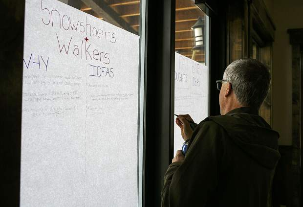Local residents write their opinions on posters during the