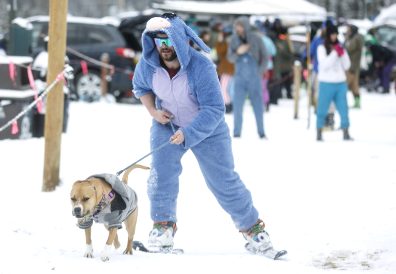 A man in the easter bunny suit is towed towards the chairlift with his dog Sunday, April 1, at Arapahoe Basin. The ski resort attract thousands of skiers, snowboarders, and real-life gapers in outfits every year on April Fools.