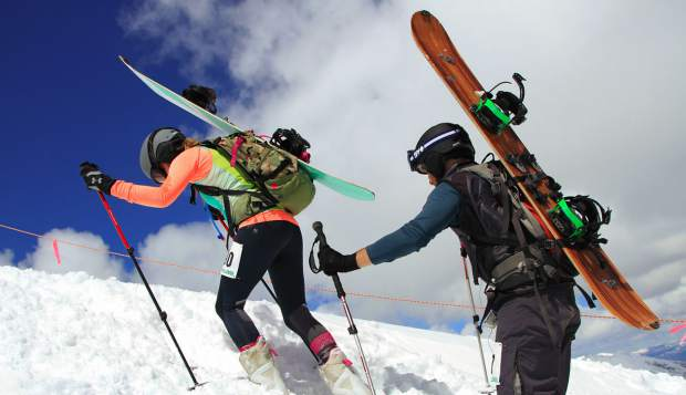 A pair of Imperial Challenge competitors use their treeking poles to ascend Breckenridge Ski Resort while carrying their snowboards on their backs during the 2017 Imperial Challenge pseudo-triathlon race.