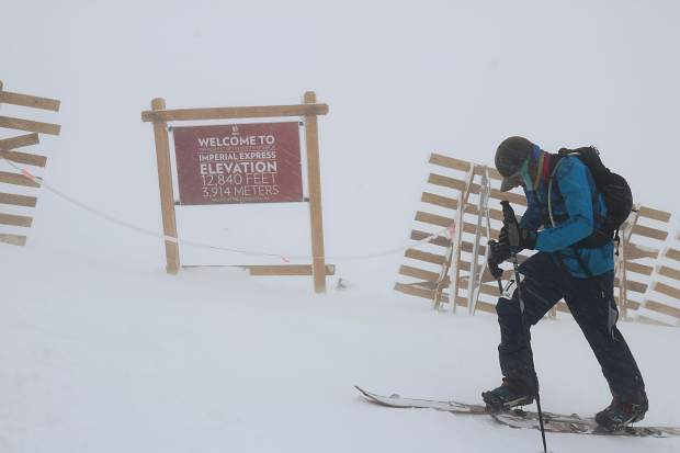 A competitor braces against the wind and blowing snow as he skins up the Imperial Challenge 'pseudo triathlon' race course past the Imperial Express lift, the highest lift in North America at 12,840 feet.