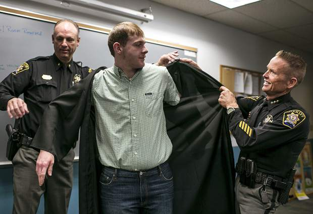 Detentions Commander David Bertling, left, and Sheriff Jaime FitzSimons help inmate Tyler Little into a graduation gown to celebrate the completion of his GED.