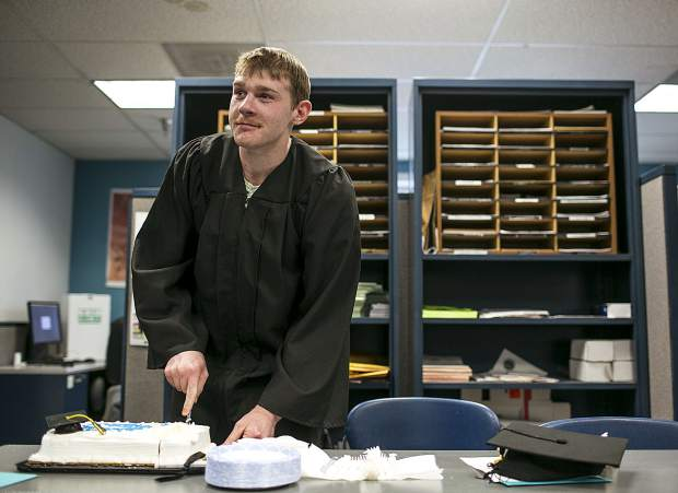 Summit County Jail inmate Tyler Little cuts a celebratory cake after receiving his GED.