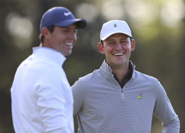 Matt Parziale, right, the U.S. Mid-Amateur champion who works as a firefighter in his hometown in Massachusetts, shares a laugh with Rory McIlroy on the first green during a practice round for the Masters golf tournament at Augusta National Golf Club in Augusta, Ga., Monday, April 2, 2018, in Augusta.