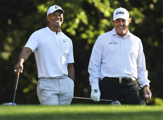 Tiger Woods, left, and Phil Mickelson share a laugh on the 11th tee box while playing a practice round for the Masters golf tournament at Augusta National Golf Club in Augusta, Ga., Tuesday, April 3, 2018.