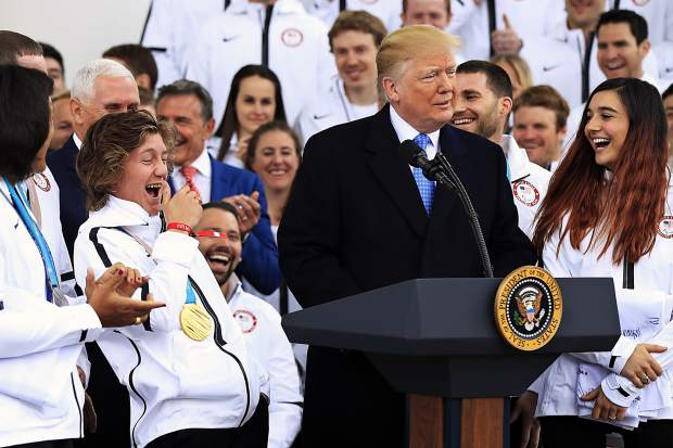 Olympic gold medalist snowboarder Redmond Gerard, left, reacts to a comment from President Donald Trump during a ceremony welcoming the Team USA Olympic athletes on North Portico at the White House in Washington, Friday, April 27, 2018.