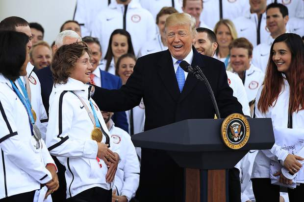 Olympic gold medalist snowboarder Redmond Gerard, left, listens to President Donald Trump describing his snowboarding stunts during a ceremony welcoming the Team USA Olympic athletes on North Portico at the White House in Washington, Friday, April 27, 2018. (AP Photo/Manuel Balce Ceneta)