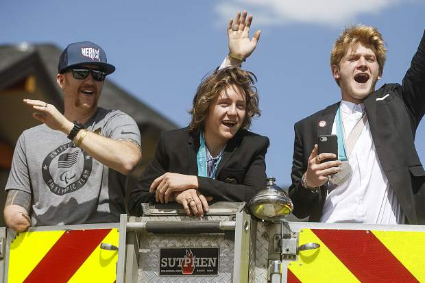 Hailing from Silverthorne, 2018 paralympian Jimmy Sides, far left, and the 2018 winter olympians, gold medalist Red Gerard, and silver medalist Kyle Mack wave to the crowds from the fire truck during the parade on Rainbow Drive Saturday, April 28, in Silverthorne.