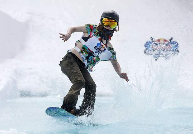A snowboarder rides on water in the Red Bull Slopesoakers Pond Skimming competition Saturday, April 14, at Copper Mountain.