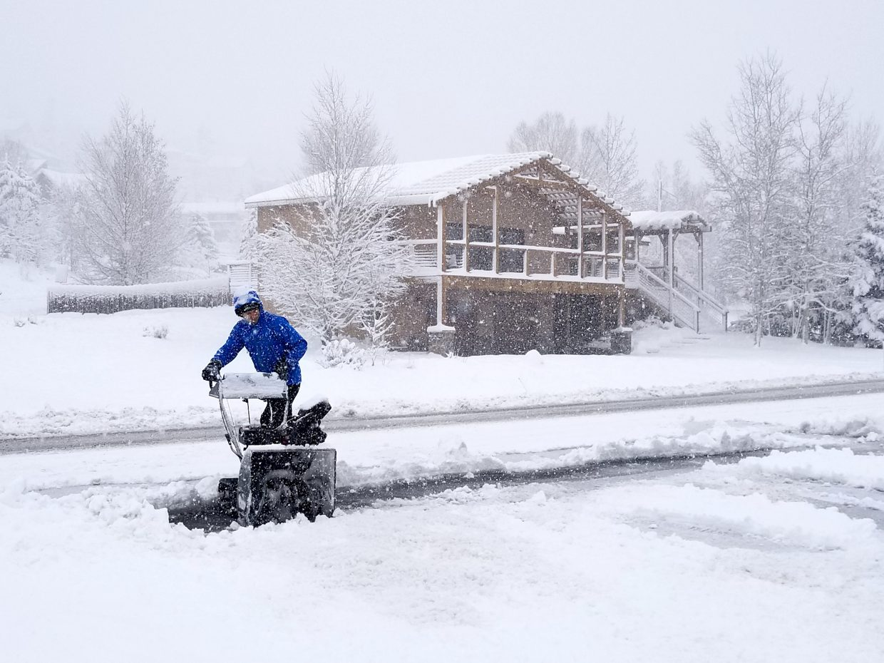 A Summit Cove resident gets out the snow blower to clear his driveway this morning.