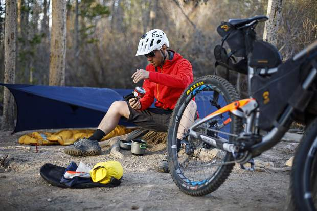 Zach Husted demonstrates bikepacking while at Rainbow Lake on Tuesday in Frisco. Husted went on an 11-day, 539-mile trip on the Colorado Trail via his mountain bike late last September.