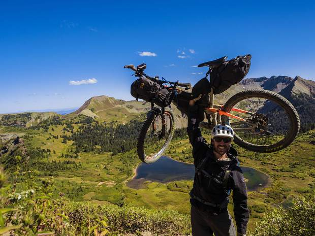 Zach Husted raises his 40-pound bikepack during his 11-day, 539-mile trip on and around the Colorado Trail via his mountain bike late last September.