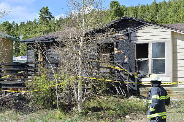 A fireman with the Red, White and Blue Fire Protection District surveys the damage after a house fire severely damaged a home at 106 Reliance Drive in Breckenridge on Sunday.