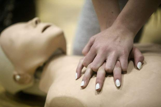 Summit High School students take turns performing CPR using the practice manikin during the second annual Hands Only CPR day Thursday.