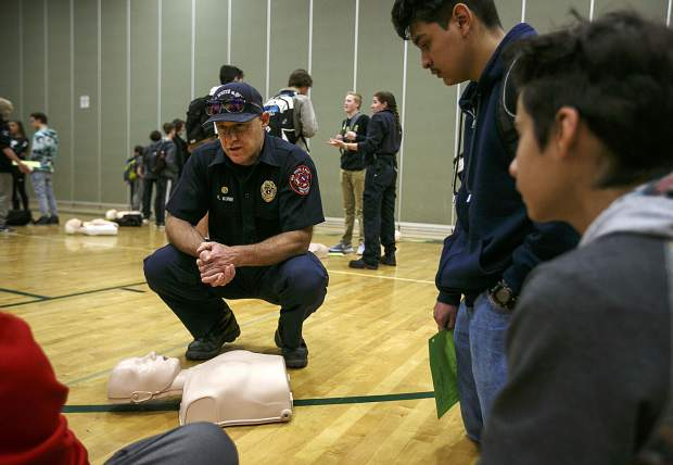 A firefighter with Red, White and Blue Frie Protection District leads a group tutorial on how to perform CPR.
