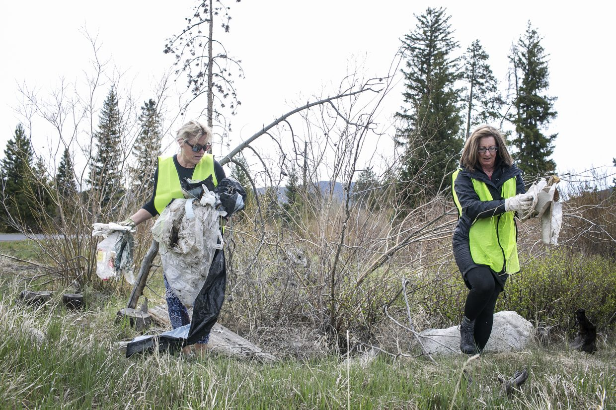 Frisco residents Susanne Johnston, left, and Sandy Kuschnerus carry trash found along Highway 9 during the town clean up day Saturday, May 19, in Frisco.