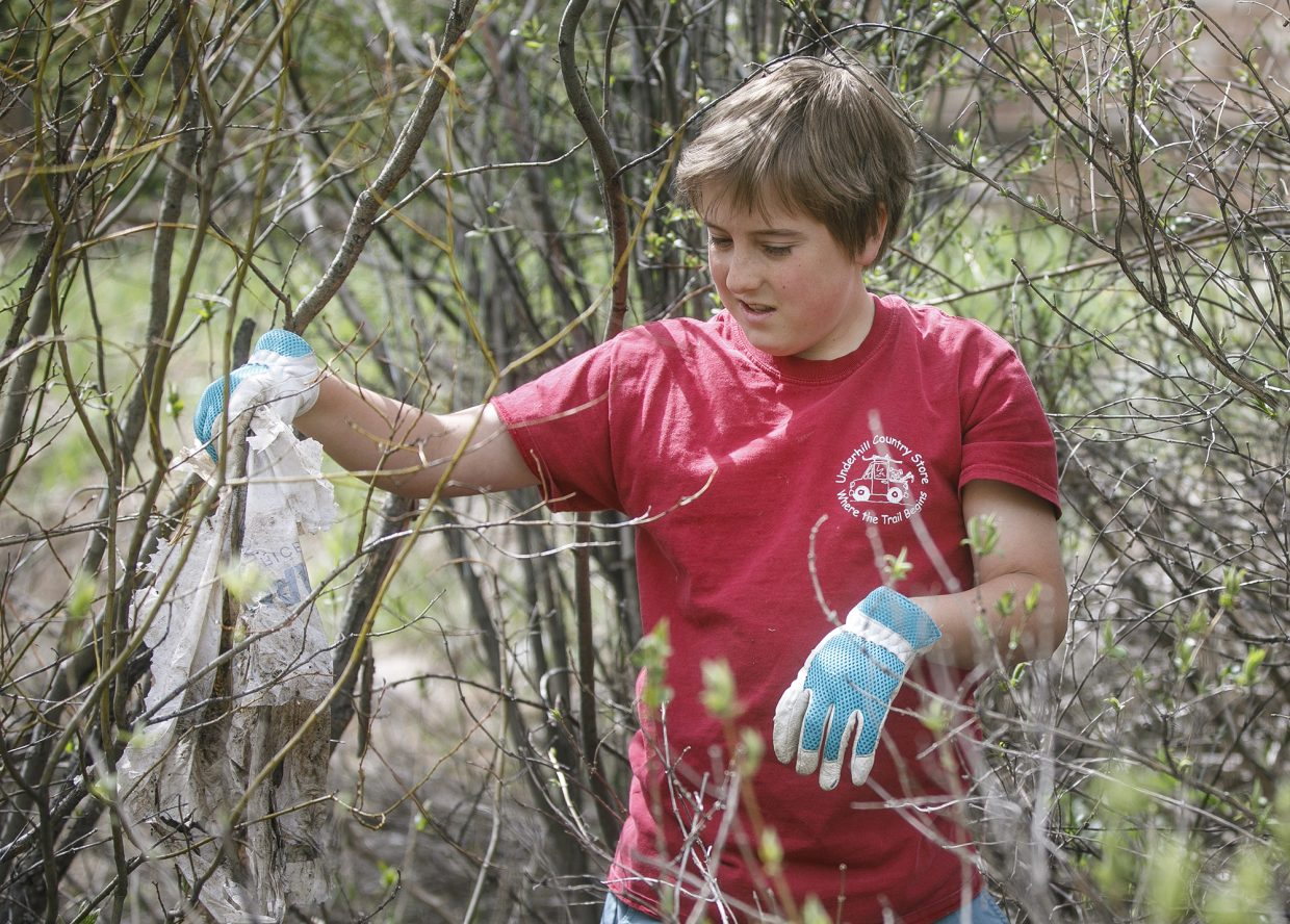 Leif Anderso, 13, finds an old grocery store plastic bag in along the Recreational Pathway in Frisco during the town clean up day Saturday, May 19.