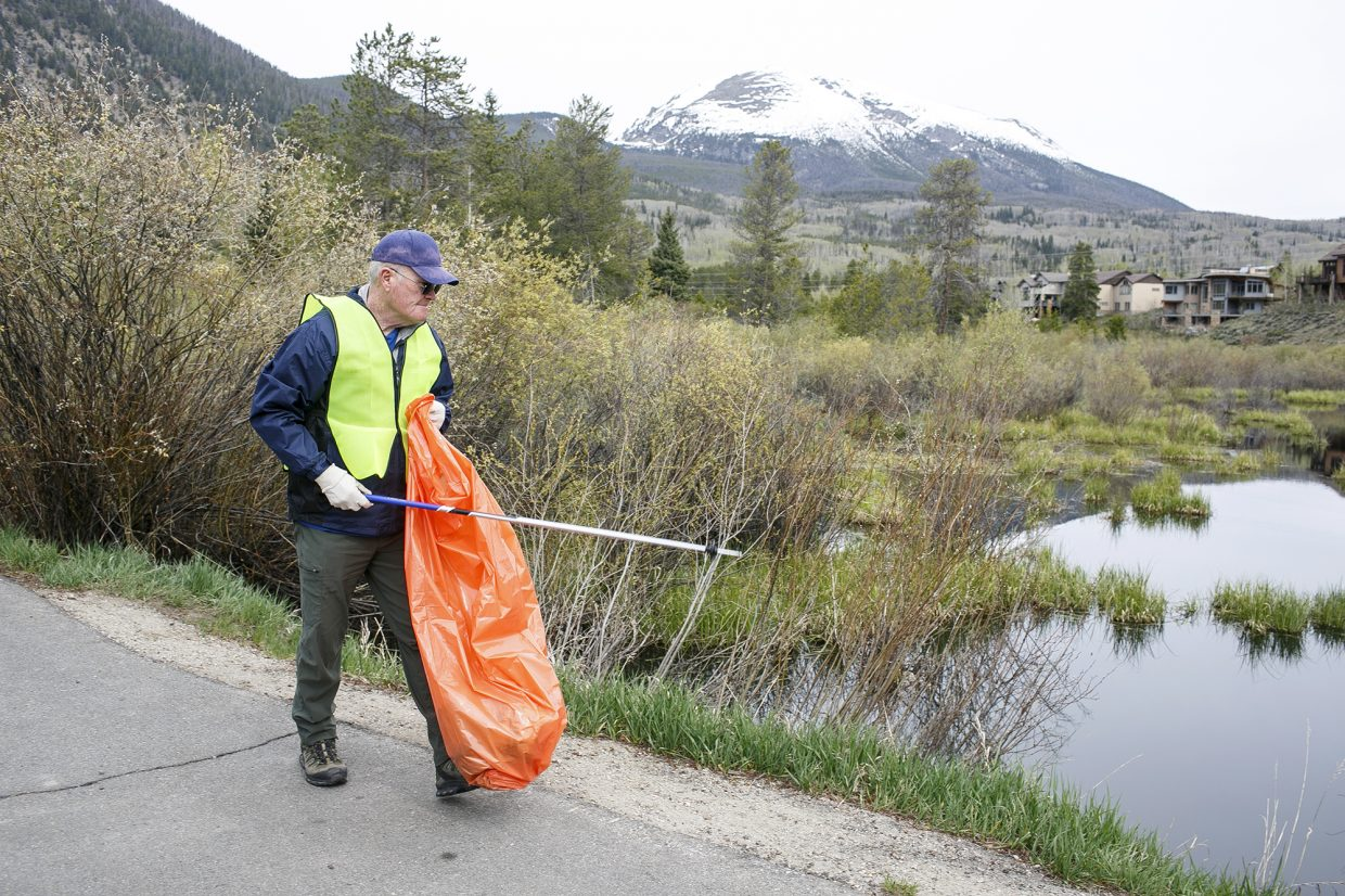 Frisco resident Tim Rawley picks up trash near Walter Byron Memorial Park during the town clean up day Saturday, May 19, in Frisco.
