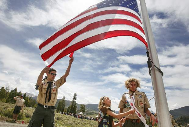 Summit County Boy Scout and Cub Scout members, Morgan McGuire, from left, Lydia Ashley, and Jeremiah Vaille raise a new flag during the Memorial Day ceremony Monday, May 28, at the Dillon Cemetery.