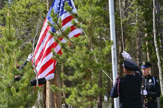 Breckenridge police and officials with the Red, White and Blue Fire Protection District raise the flag Monday during the sixth Memorial Day Commemoration at Valley Brook Cemetery in Breckenridge.