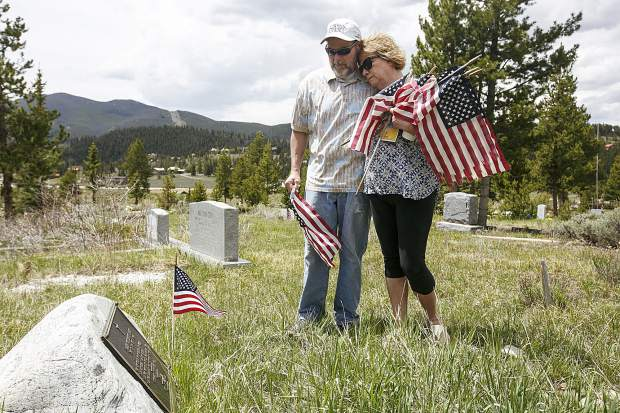 Silverthorne residents Bill and Val Crangle take a moment at the grave of Val's father, James Hart, a retired Master Staff Sargent in the U.S. Air Force who passed away in 1995, while replacing the older American flags with new ones following the Memorial Day ceremony Monday, May 28, at the Dillon Cemetery. Hart, who died at age 59 in Summit County, suffered PTSD from two tours in the Air Force during the Vietnam War era.
