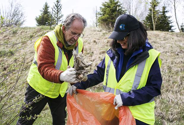 Summit County residents Paul and Gay Nastaszrwski pick up trash along Highway 9 during the clean up day Saturday, May 19, in Frisco.