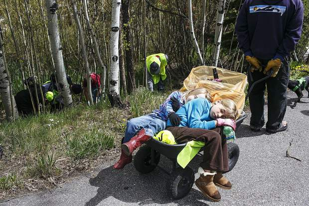 Josephine Anderson, 5, left, and Peyton Goossen, 10, take a nap in the wheel barrow towards the end of the town clean up day Saturday, May 19, in Frisco.