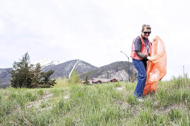 Silverthorne resident Linda bannister pick up trash found along Highway 9 during the town clean up day Saturday, May 19, in Frisco.