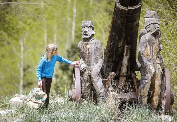 Peyton Goossen, 10, discovers a wooden statue while picking up trash near Highway 9 during the town clean up day Saturday, May 19, in Frisco.