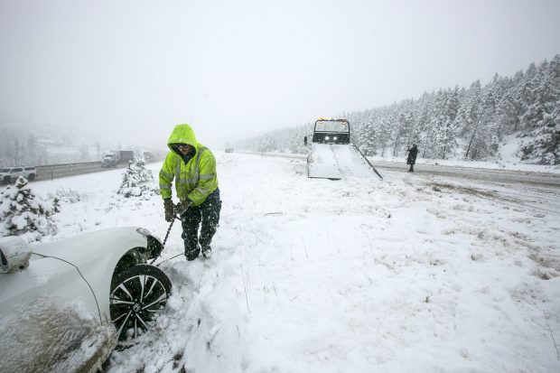 Ryan's Recovery employee William Singer works to tow a spun out vehicle along interstate 70 Thursday, May 3, in Silverthorne.