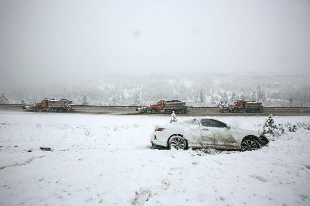 Snowplows pass a spun-out vehicle along interstate 70 Thursday in Silverthorne.