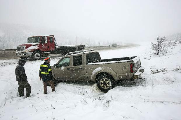 Ryan's Recovery truck works to tow a spun-out vehicle along interstate 70 Thursday in Silverthorne.