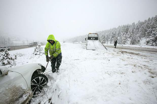 Ryan's Recovery employee William Singer works to tow a spun-out vehicle along interstate 70 Thursday in Silverthorne.