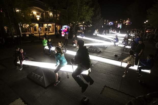 Visitors enjoy the seesaws illuminated by lights, the Impulse, by Lateral Office and CS Design, along the Blue River during the WAVE art festival Friday, June 1, in Breckenridge.
