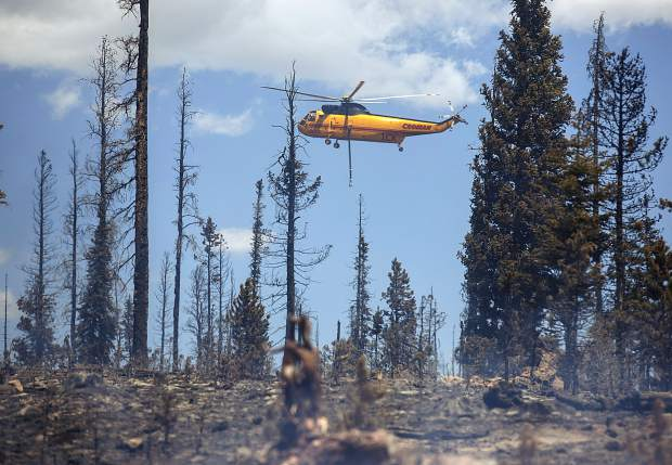 A helicopter continues to dump water on flames at the Buffalo Fire site Wednesday, June 13, near Silverthorne.