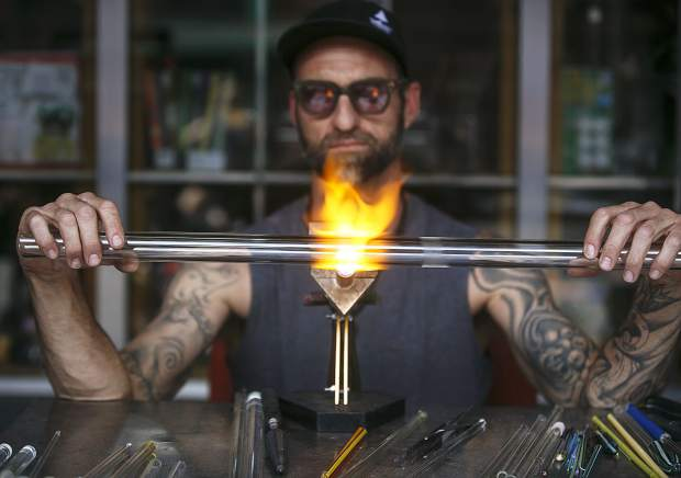 A glass pipe artist, Sean Spinato, creates a product using the flames at the Smoke N' Bra store along Main Street during the Frisco BBQ event Friday, June 15, in Frisco.