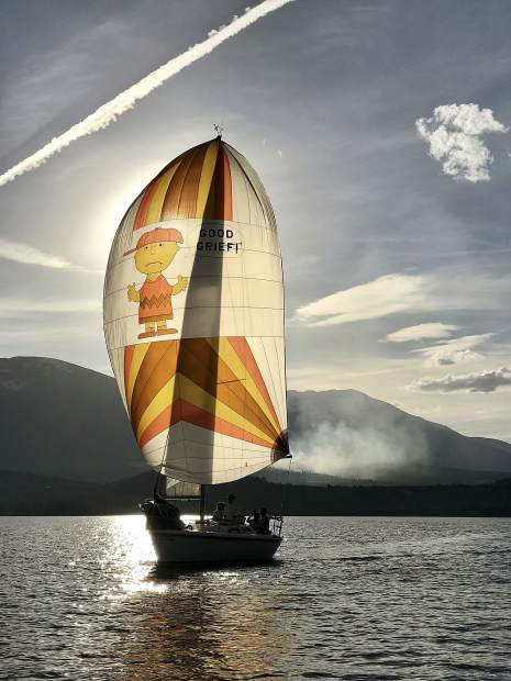"""Craig Simson's """"Charlie Brown"""" sailing while the fire burns in background."""