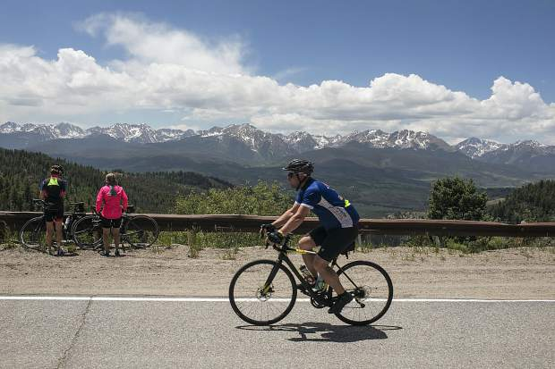 Bicyclists participating in the 33rd annual Ride the Rockies bike tour pedal on Ute Pass in June 2018 near Silverthorne with views of the Gore Range in the distance.