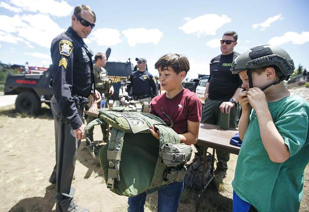 Austin Meadors, 10, center, takes a close look at the bullet proof vest used by the local sheriff department during the Safe Summer Kickoff event at Rainbow Park Saturday, June 9, in Silverthorne.