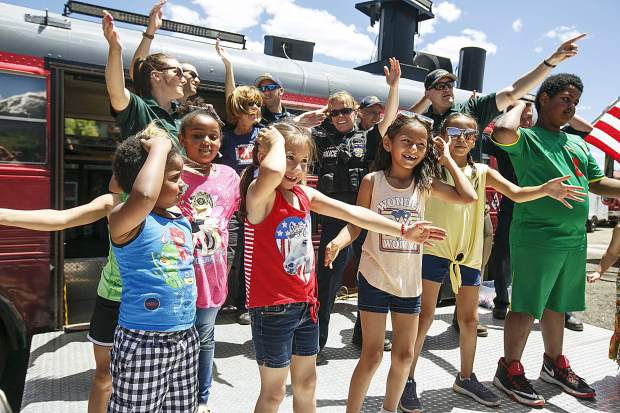 Children dance along a song with the local law enforcement and firefighters during the Safe Summer Kickoff event at Rainbow Park Saturday, June 9, in Silverthorne.