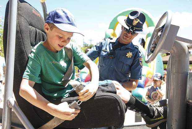 Braeden Opsahl, 9, buckles up on the Seat Belt Convincer machine as Colorado State Patrol trooper Galen Peterson looks on during the Safe Summer Kickoff event at Rainbow Park Saturday, June 9, in Silverthorne. The machine, controlled by trooper Peterson, allow the riders to feel what it is like to be stopped abruptly with the seat belt on.