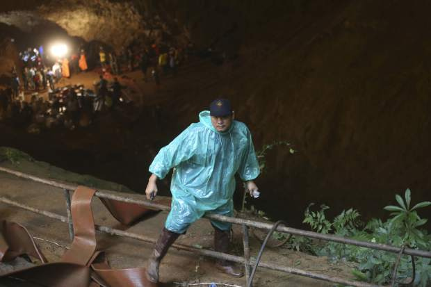 A rescue worker climbs out of the staging area at the entrance of a cave complex where it's believed that 12 soccer team members and their coach went missing, Wednesday, June 27, 2018, in Mae Sai, Chiang Rai province, northern Thailand. Rain is continuing to fall and water levels keep rising inside a cave in northern Thailand, frustrating the search for the boys and their soccer coach who have been missing since Saturday.