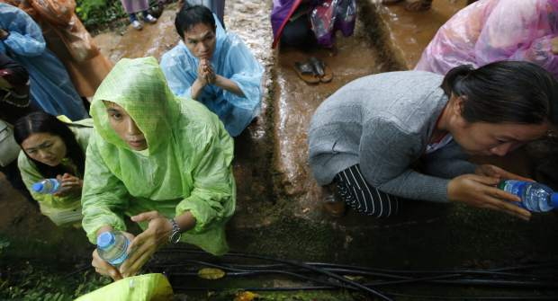 Relatives of 12 young soccer team members and their coach pray at a shrine for their rescue after going missing in a large cave, Wednesday, June 27, 2018, in Mae Sai, Chiang Rai province, northern Thailand. Rain is continuing to fall and water levels keep rising inside a cave in northern Thailand, frustrating the search for the boys and coach who have been missing since Saturday.
