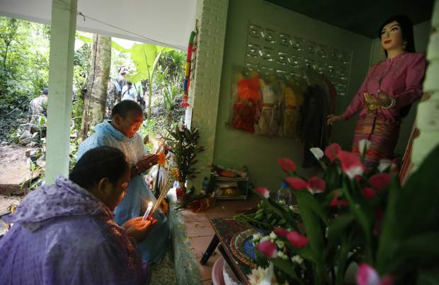 Relatives of 12 young soccer team members and their coach pray at a shrine for their rescue after going missing in a large cave, Wednesday, June 27, 2018, in Mae Sai, Chiang Rai province, northern Thailand. Rain is continuing to fall and water levels keep rising inside a cave in northern Thailand, frustrating the search for the boys and their soccer coach who have been missing since Saturday.