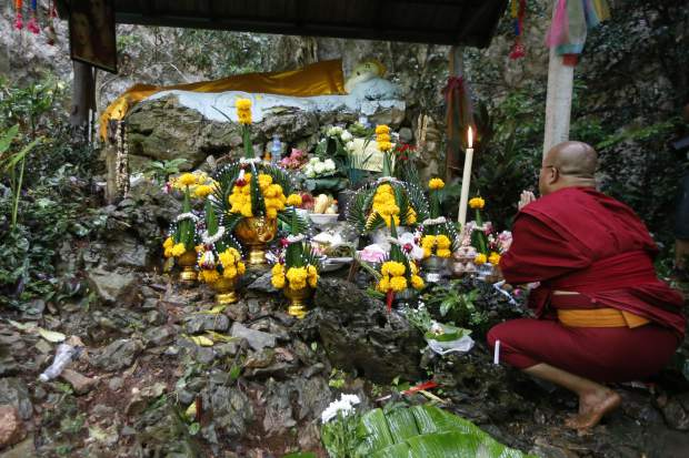 A Thai Buddhist monk pray for 12 boys and their soccer coach, in Mae Sai, Chiang Rai province, northern Thailand Wednesday, June 27, 2018. Rain continued to fall and water levels kept rising Wednesday inside a cave in northern Thailand, frustrating the search for the boys and the coach who have been missing in the sprawling underground caverns since Saturday.