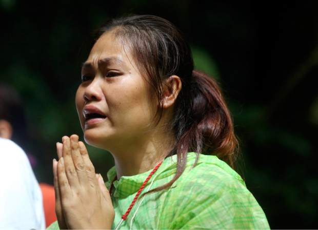 One of relatives of 12 young soccer team members and their coach prays for their rescue after going missing in Tham Luang Nang Non cave, Wednesday, June 27, 2018, in Mae Sai, Chiang Rai province, northern Thailand. Rain is continuing to fall and water levels keep rising inside a cave in northern Thailand, frustrating the search for the boys and their soccer coach who have been missing since Saturday.