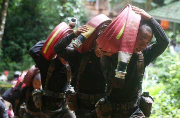 Thai soldiers bring hoses and additional water pumps to continue the search for 12 young soccer team members and their coach after going missing in Tham Luang Nang Non cave in Mae Sai, Chiang Rai province, northern Thailand Wednesday, June 27, 2018. Rain is continuing to fall and water levels keep rising inside a cave in northern Thailand, frustrating the search for the 12 boys and their soccer coach who have been missing since Saturday.