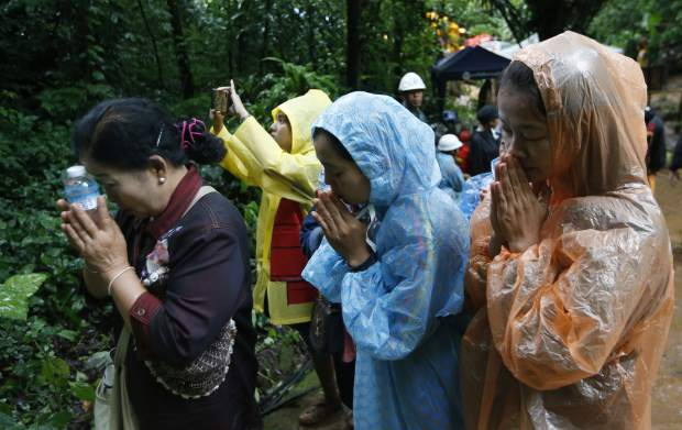 Relatives of 12 young soccer team members and their coach pray for their rescue after going missing in a large cave, Wednesday, June 27, 2018, in Mae Sai, Chiang Rai province, in northern Thailand. Rain is continuing to fall and water levels keep rising inside a cave in northern Thailand, frustrating the search for 12 boys and their soccer coach who have been missing since Saturday.