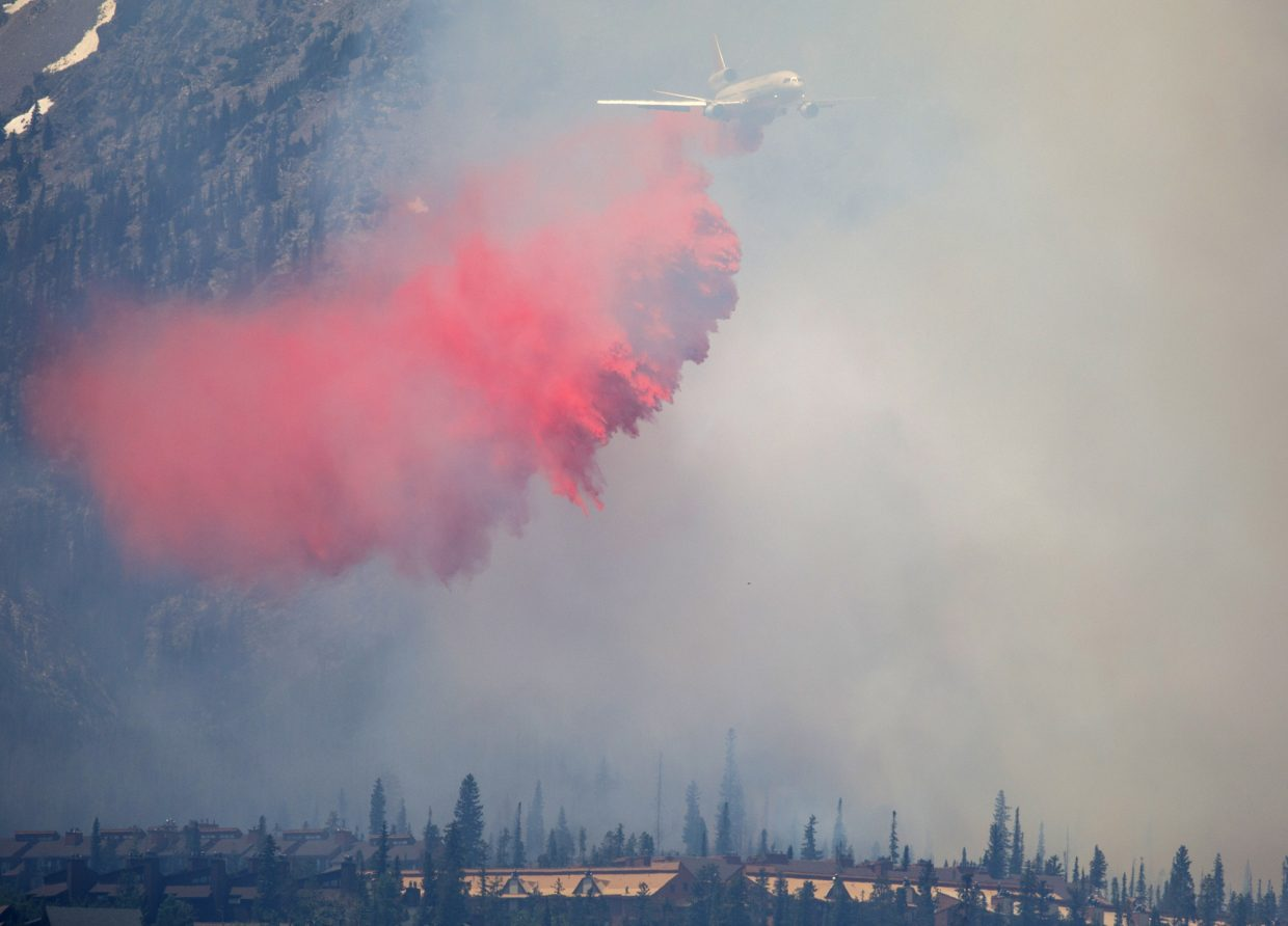 A fire retardant aircraft flies over the wildland fire in the Wildernest neighborhood Tuesday, June 12, 2018, near Silverthorne.